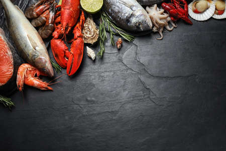Fresh fish and different seafood on black table, flat lay. Space for text 版權商用圖片