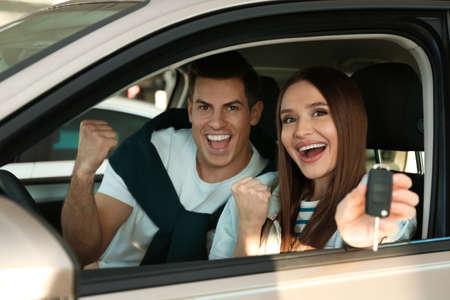 Pareja feliz con llave de coche sentado en auto moderno en concesionario Foto de archivo