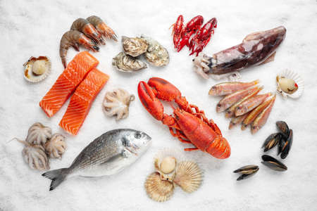 Fresh fish and seafood on ice, flat lay
