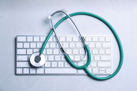 Keyboard and stethoscope on grey stone table, top view. Concept of technical support Standard-Bild - 138446601