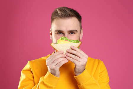 Young man eating tasty sandwich on pink background