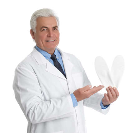 Male orthopedist showing insoles on white background