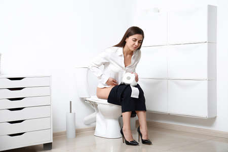 Woman with stomach ache sitting on toilet bowl in bathroom