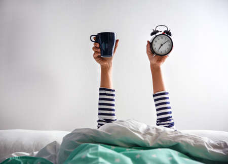 Woman with cup and alarm clock lying in bed, closeup. Morning time Banco de Imagens