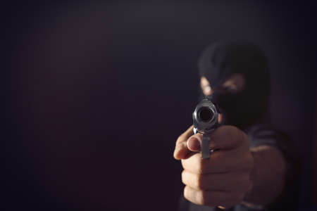 Professional killer on black background, focus on gun. Space for text