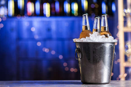 Beer in metal bucket with ice on table against blurred lights. Space for text Stock fotó