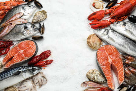 Fresh fish and seafood on ice, flat lay. Space for text 版權商用圖片