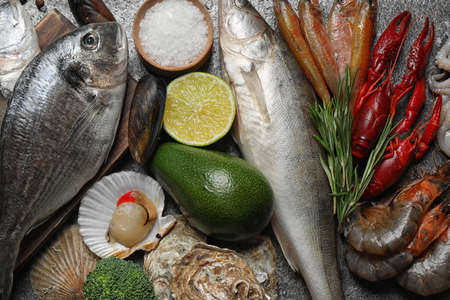 Fresh fish and different seafood on grey table, top view 版權商用圖片