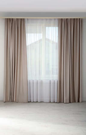 Raam met elegante gordijnen in lege ruimte