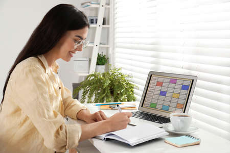 Young woman planning her schedule with calendar app on laptop in office Stock Photo