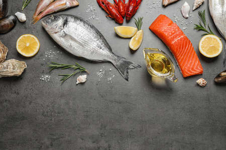 Fresh fish and seafood on grey table, flat lay. Space for text