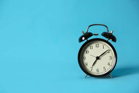 Alarm clock on light blue background, space for text. Morning time