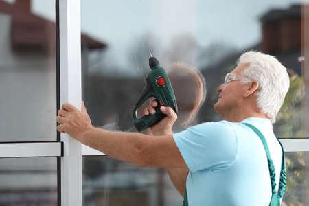 Reifer Bauarbeiter repariert Kunststofffenster mit Elektroschrauber im Innenbereich