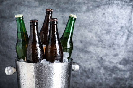 Beer in metal bucket with ice on grey background. Space for text Stock fotó