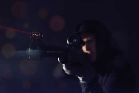 Professional killer on black background, focus on sniper rifle