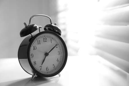 Alarm clock on windowsill, space for text. Morning time