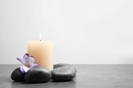 Spa stones, burning candle and freesia flower on grey table, space for text