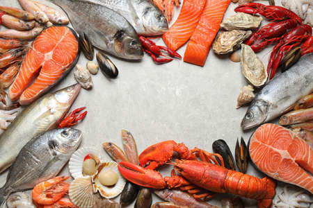 Fresh fish and different seafood on light grey table, flat lay. Space for text 版權商用圖片