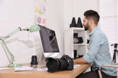 Professional photographer working at table in office, focus on camera Stock Photo