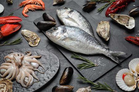 Fresh fish and different seafood on black table 版權商用圖片