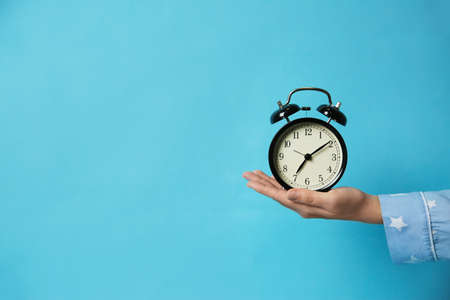 Closeup view of woman holding alarm clock on light blue background, space for text. Morning time Banco de Imagens