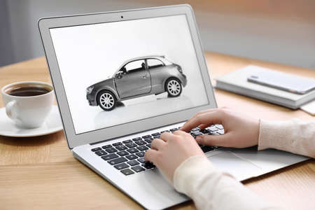 Mujer con portátil para comprar coche en la mesa de madera en el interior, primer plano