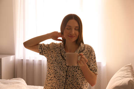 Young woman with drink on bed at home. Lazy morning Banco de Imagens