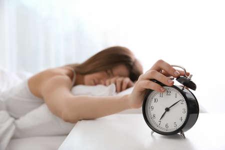 Jeune femme éteignant le réveil à la maison le matin, se concentrer sur la main