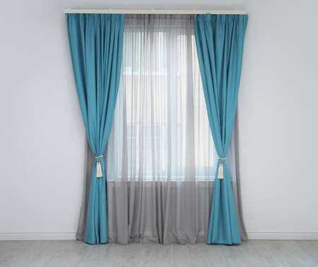 Window with elegant curtains in empty room
