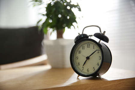 Alarm clock on wooden table at home. Morning time
