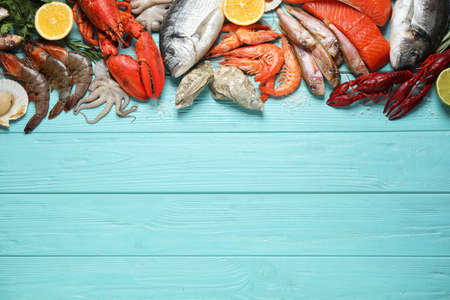 Fresh fish and different seafood on blue wooden table, flat lay. Space for text 版權商用圖片