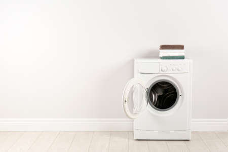 Modern washing machine with stack of towels near white wall, space for text. Laundry day