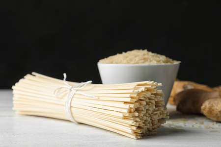 Raw rice noodles on white wooden table, closeup