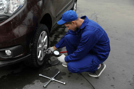 Worker checking tire pressure in car wheel at service station