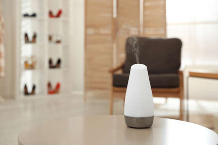 Aroma oil diffuser on table indoors, space for text. Air freshener
