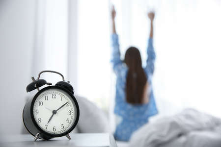 Young woman stretching at home in morning, focus on alarm clock
