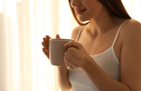 Young woman with cup near window at home, closeup. Lazy morning Banco de Imagens