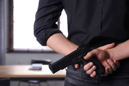 Man holding gun indoors, closeup. Dangerous criminal