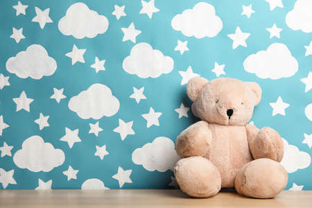 Teddy bear on wooden table near wall with painted blue sky, space for text. Baby room interior
