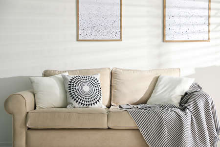 Stylish decorative pillows on beige couch indoors 写真素材