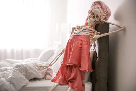 Human skeleton in silk pajamas and towel sitting on bed indoors