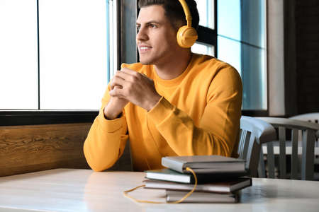 Man with headphones connected to book at table in cafe
