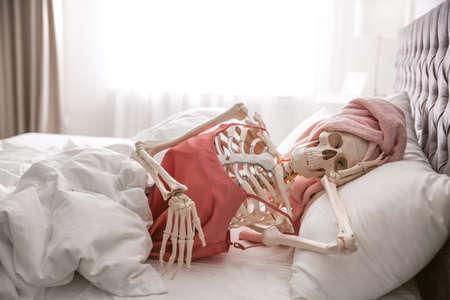 Human skeleton in silk pajamas and towel lying on bed indoors Banco de Imagens