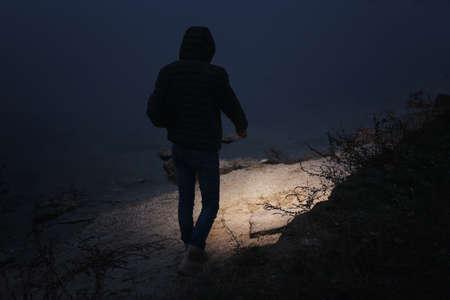 Man with flashlight walking near river in evening Stockfoto