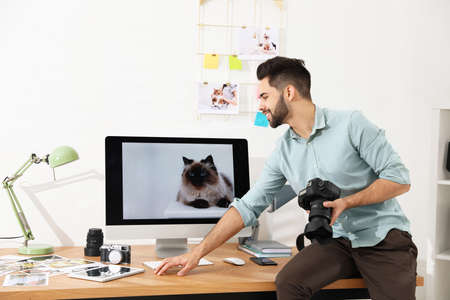 Professional photographer with camera working in light modern office Stock Photo
