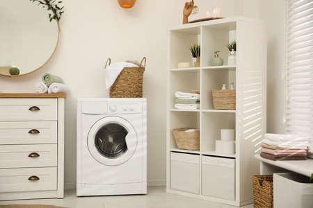 Modern washing machine near white wall in elegant bathroom Stock Photo