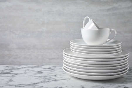 Set of clean dishware on marble table. Space for text