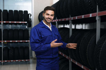 Male mechanic near rack with tires in auto store