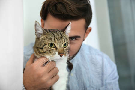 Man with tabby cat near window at home. Friendly pet Imagens