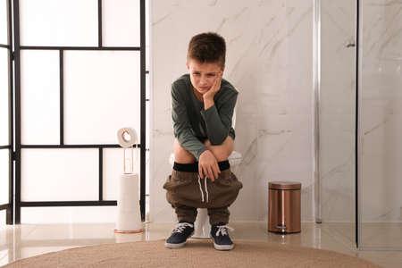 Jongen lijdt aan aambei op toiletpot in toilet Stockfoto